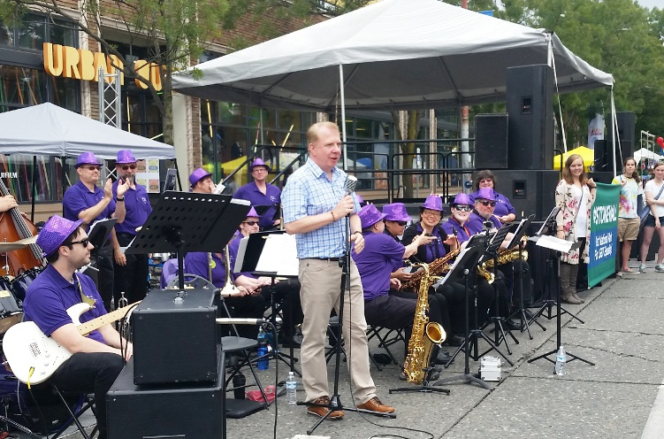 Mayor speaking in front of Purple Passion band